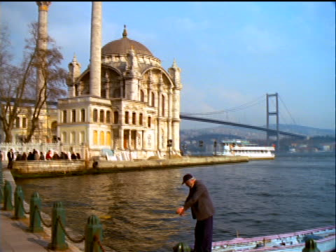 tilt up from senior man in rowboat to ortakoy mosque with bosporus bridge in background / istanbul, turkey - ortakoy mosque stock videos and b-roll footage