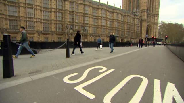 Tilt up from Slow sign on road to exterior of Houses of Parliament Westminster