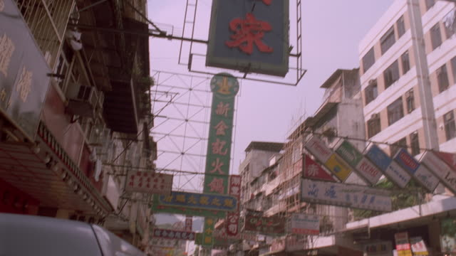 vídeos y material grabado en eventos de stock de tilt up from street and signs to airliner flying low overhead / kowloon, kai tek, hong kong - kowloon