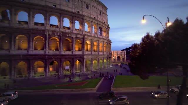 tilt up from street to illuminated colosseum at night - arch of constantine stock videos and b-roll footage