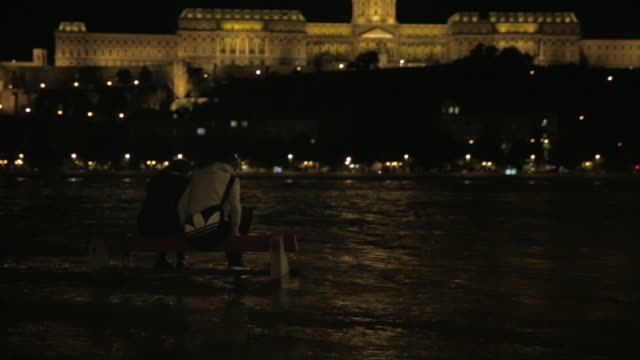 tilt up from students on a bench to buda castle at night - royal palace of buda stock videos & royalty-free footage