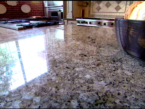 tilt up from the granite counter to show a basket of bread and the kitchen. - granite stock videos and b-roll footage
