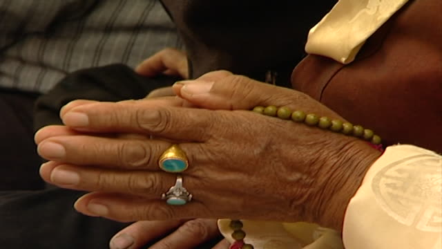 tilt up from the hands of an elderly tibetan worshipper clasped in prayer to her face as she listens to hh dalai lama the 14th dalai lama lives in... - worshipper stock videos & royalty-free footage