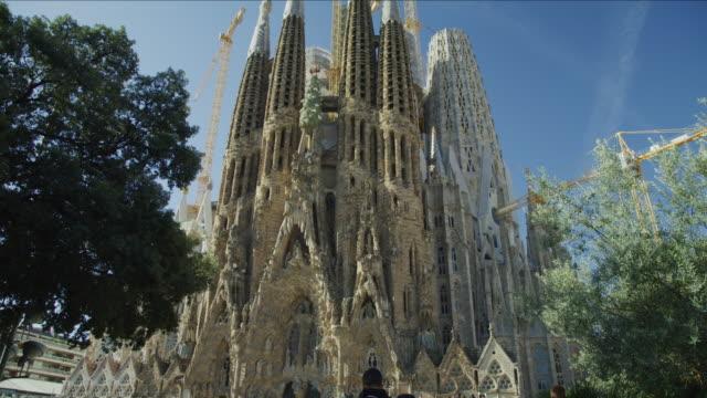 Tilt up from tourists admiring La Sagrada Familia to towers and cranes / Barcelona, Barcelona, Spain