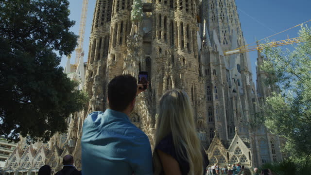 tilt up from tourists photographing la sagrada familia to towers and cranes / barcelona, barcelona, spain - tourist stock videos & royalty-free footage