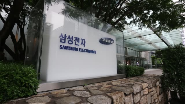 Tilt up from traffic and pedestrians to the Samsung Electronics Co Seocho office building in Seoul A sign for Samsung Electronics sits outside the...