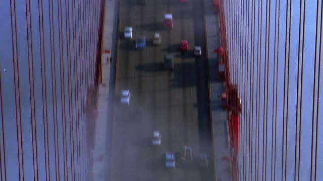 vídeos y material grabado en eventos de stock de tilt up from traffic on foggy golden gate bridge to tower / san francisco, california - imagen virada