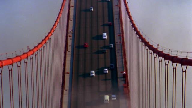 vídeos y material grabado en eventos de stock de tilt up from traffic on golden gate bridge to top of tower immersed in fog / san francisco, california - puente golden gate