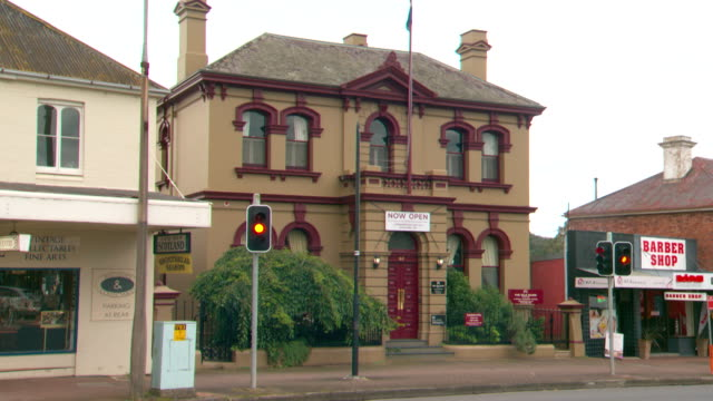 Tilt up from traffic on intersection of Main Street Bowral Rd to 'The Old Bank' building / flag on pole and 'Now Open' sign out the front of colonial...