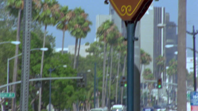 tilt up from traffic on street to beverly hills sign / california - ビバリーヒルズ点の映像素材/bロール