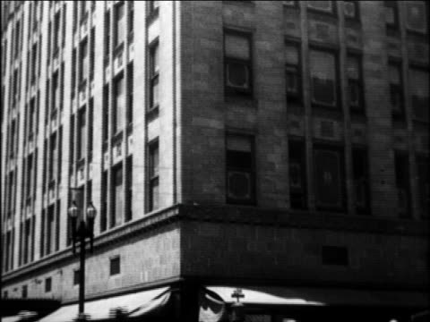 b/w 1924 tilt up from traffic + people on city street to corner of building / newsreel - 1924 stock videos and b-roll footage