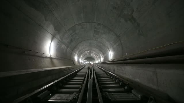 tilt up from train tracks to workers they fix cable support trays to the access tunnel wall inside the west section of the gotthard base tunnel in... - 断面点の映像素材/bロール