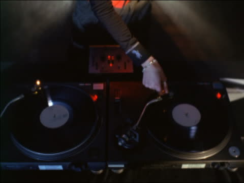 vidéos et rushes de tilt up from two turntables to female dj with shaved head wearing flashlight goggles / takes off headphones - platine de disque vinyle