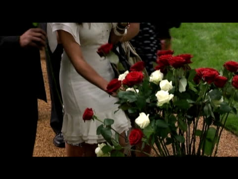 tilt up from vase containing white and red roses to people paying respect to 7/7 bombing victims in new memorial garden london 7 july 2009 - temporäre gedenkstätte stock-videos und b-roll-filmmaterial