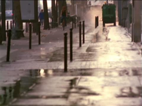 tilt up from wet pavement to woman riding bicycle + street cleaner on sidewalk lined by trees / Paris