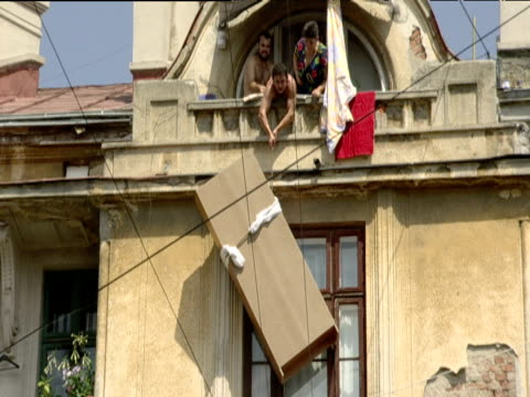 vídeos y material grabado en eventos de stock de tilt up from woman on street to men and woman hoisting wardrobe on rope up side of building bucharest - rumania