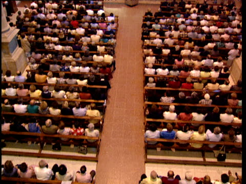 stockvideo's en b-roll-footage met tilt up from worshippers sat listening to priest during mass in catholic church basque country spain - gelovige