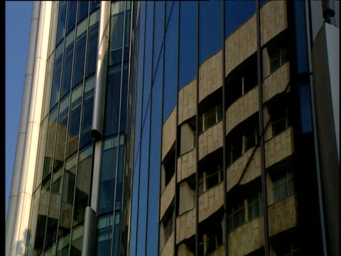 tilt up front of modern glass fronted building against blue sky - fensterfront stock-videos und b-roll-filmmaterial