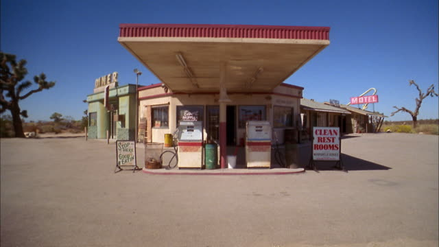 """tilt up gas station w/gas pumps and sign """"clean rest rooms"""" in foreground - gas station stock videos & royalty-free footage"""