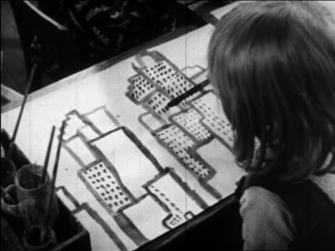 b/w 1945 tilt up girl painting skyscrapers to other children painting in classroom / educational - easel stock videos and b-roll footage
