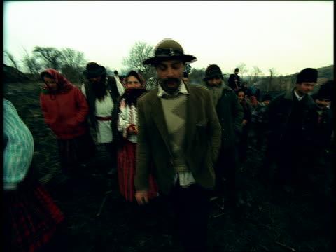 tilt up group of people in native dress walk toward camera in muddy field / Sibiu, Transylvania, Romania