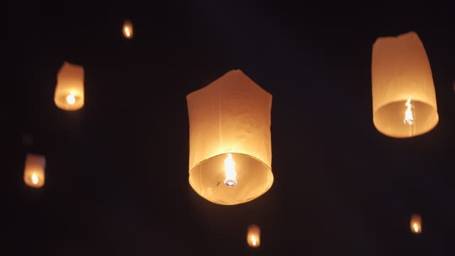 slo mo tilt up hand releasing lantern to the sky in yee peng festival (yi peng) - sky lantern stock videos & royalty-free footage
