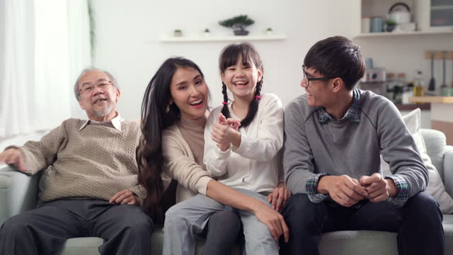4k uhd tilt up: happy multigenerational asian family looking television together on sofa in living room. - cable tv stock videos & royalty-free footage