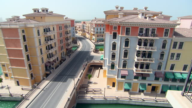 tilt up: highway crosses over green canal and through large colorful mediterranean style hotels in sunshine - doha, qatar - qatar stock videos & royalty-free footage