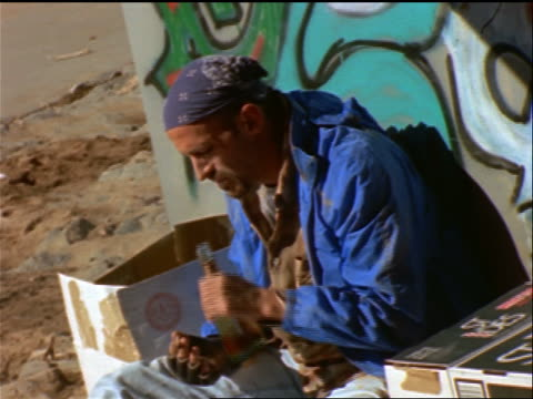 vídeos y material grabado en eventos de stock de tilt up homeless man sitting against graffiti-covered wall drinking from bottle of liquor + smoking - 1990