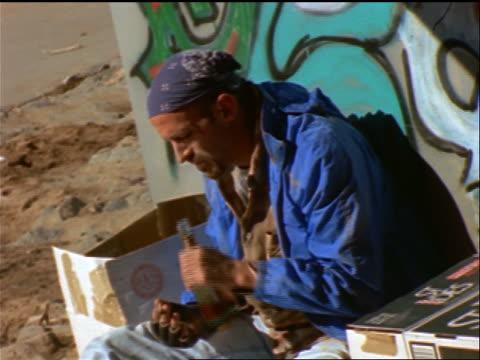 vídeos de stock e filmes b-roll de tilt up homeless man sitting against graffiti-covered wall drinking from bottle of liquor + smoking - 1990