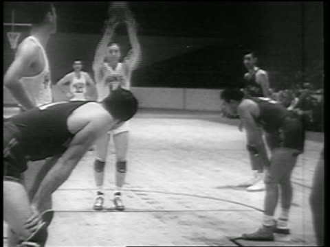 b/w 1946 tilt up huskies player making basket in free throw in game vs ny knicks - 1946 stock videos and b-roll footage
