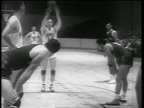 B/W 1946 tilt up Huskies player making basket in free throw in game vs NY Knicks