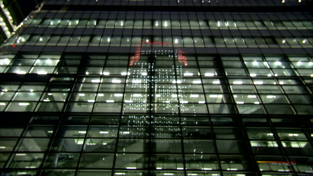 tilt up illuminated windows of office block in canary wharf at night. available in hd. - office block exterior stock videos & royalty-free footage