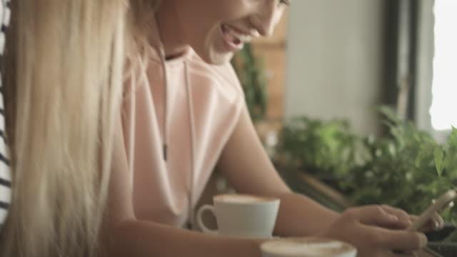 vídeos de stock e filmes b-roll de tilt up, lesbian couple on cellphone in coffee shop - cabelo curto comprimento de cabelo