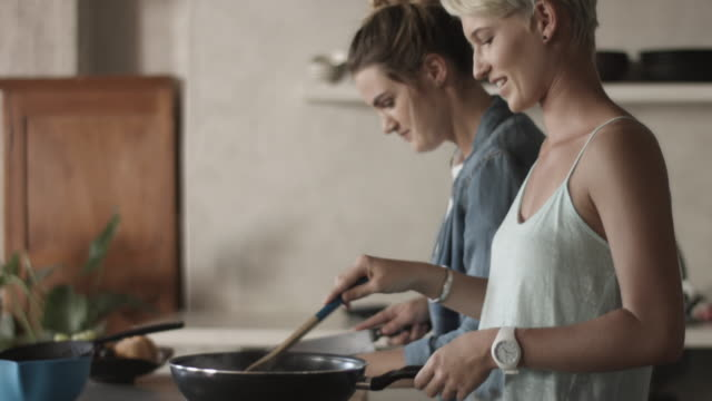 vídeos y material grabado en eventos de stock de tilt up, lesbian couple prepare dinner - cabello corto