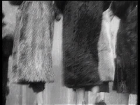 b/w 1936 rear view tilt up line of women modeling fur coats at rockefeller center, nyc - 毛皮のコート点の映像素材/bロール