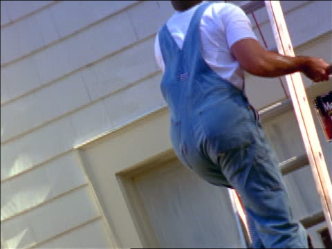 rear view tilt up man climbing ladder carrying paint can + brush to top of house - ladder stock videos & royalty-free footage