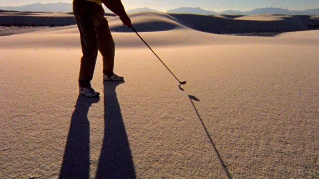 tilt up man hitting golf ball in desert / white sands, new mexico - berretto da baseball video stock e b–roll
