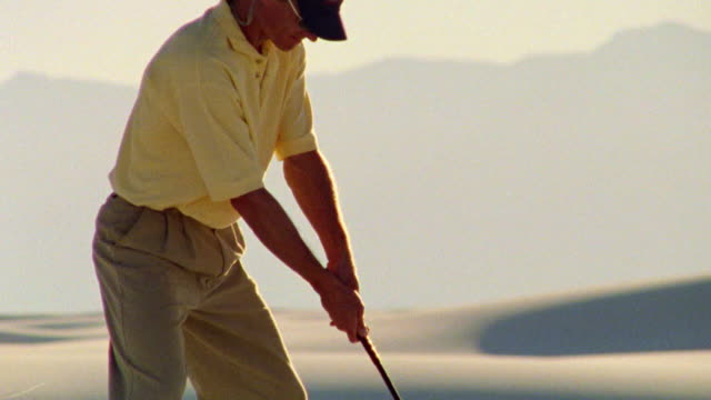 vídeos de stock, filmes e b-roll de tilt up man hitting golf ball in desert / white sands, new mexico - camisa pólo
