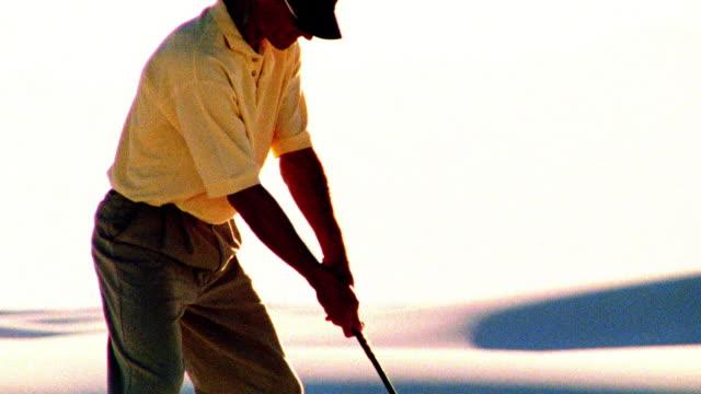 OVEREXPOSED SELECTIVE FOCUS tilt up man hitting golf ball in desert / White Sands, New Mexico