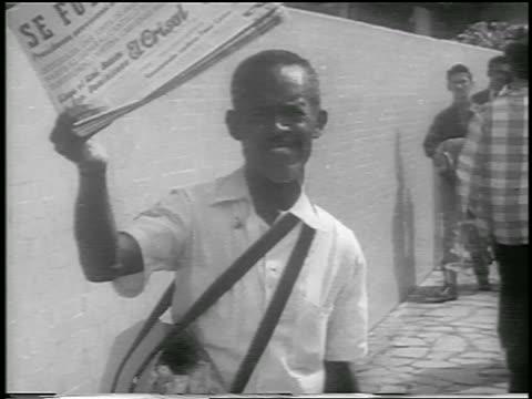B/W 1959 tilt up man holding newspaper with revolution headline / Havana / newsreel