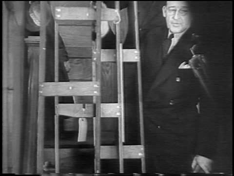 tilt up man in suit holding ladder / evidence in lindbergh kidnapping trial / nj / newsreel - 1935 stock videos & royalty-free footage