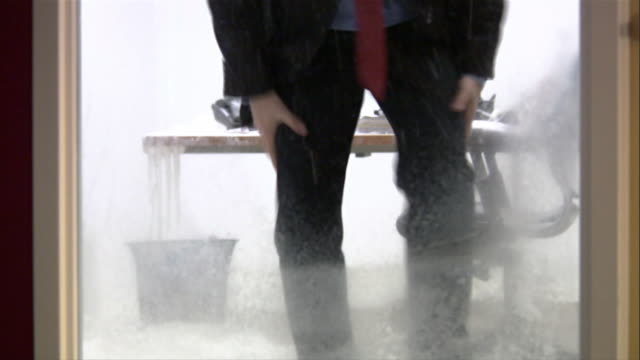 vidéos et rushes de tilt up man in suit shivering inside frozen office / waving at coworker passing by in hallway - frais