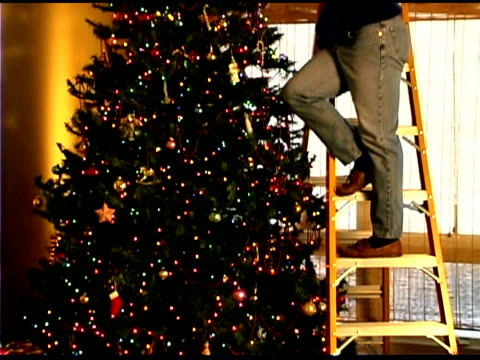 tilt up man on ladder adjusting star on christmas tree - 10秒或更長 個影片檔及 b 捲影像