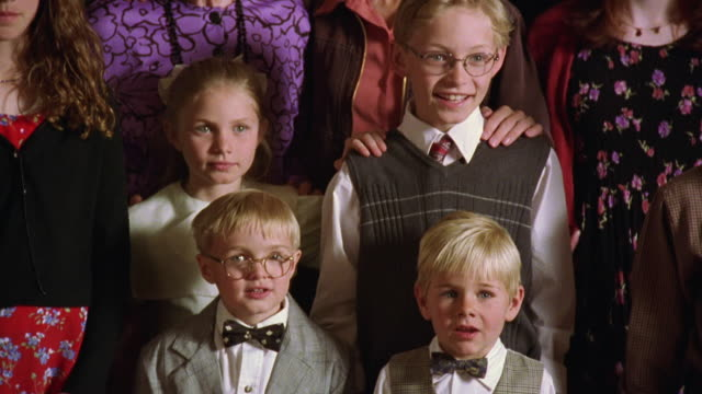 Tilt up medium shot group of blonde children smiling while posing for family photo with one shouting