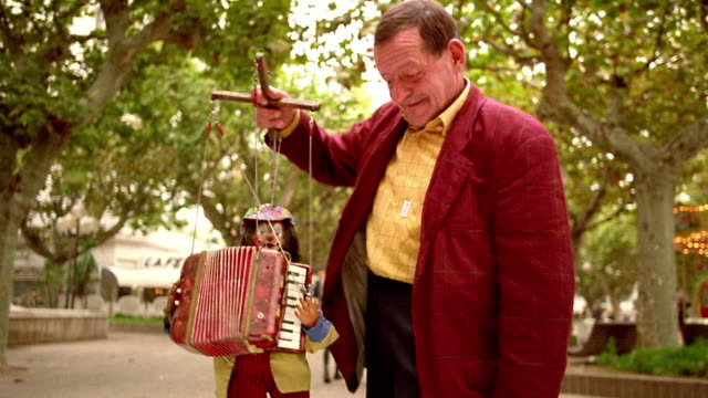 vídeos y material grabado en eventos de stock de tilt up medium shot middle age puppeteer dancing and controlling puppet with accordion outdoors / cannes, france - acordeonista