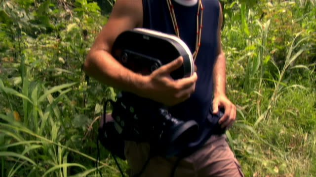 Tilt up medium shot of man holding movie camera / tilt down to jungle floor / The Amazon, Brazil