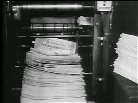 b/w 1927 tilt up newspapers coming out of printing press into stack / man grabs them / newsreel - pressa da stampa video stock e b–roll
