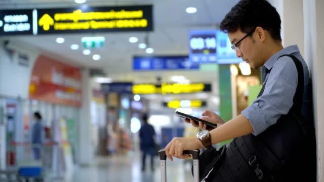 vídeos y material grabado en eventos de stock de incline hacia arriba del hombre asiático con el equipaje usando el teléfono móvil y camine lejos cuando viene el tiempo - viaje de negocios