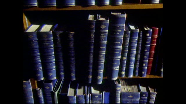 tilt up of blue hardback books on bookshelf - saggezza video stock e b–roll